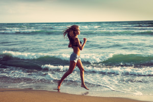 young woman run on sandy beach by the sea at sunset